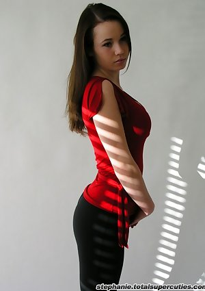 Steph postures in her red top in a studio