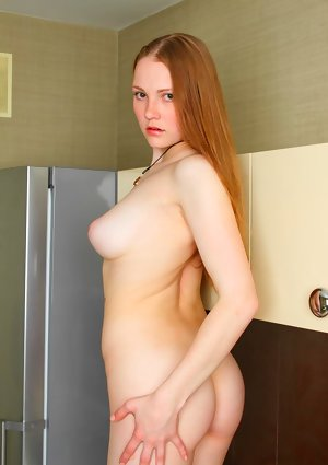 Young solo girl uncovers her big natural tits as she gets naked in the kitchen