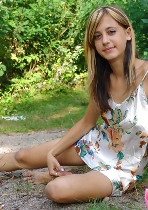 Young looking amateur flashes her upskirt panties while barefoot by trees