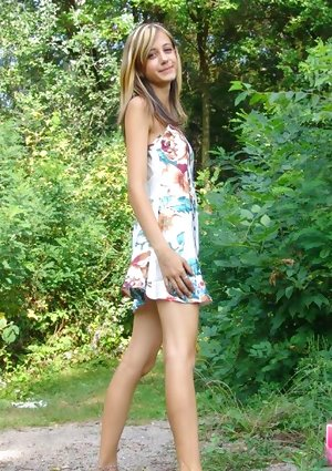 Adolescent amateur flashes her upskirt shorts by doing barefoot by trees