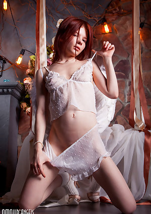 Young redhead Renzi strikes tempting solo poses in see thru lingerie