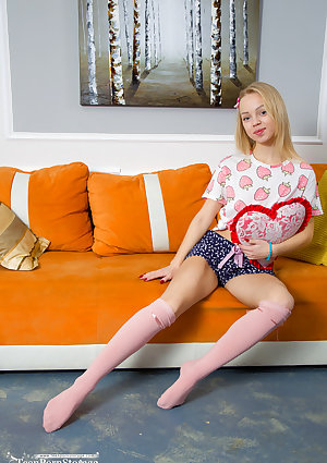 Skinny blonde teen Estel gets totally naked on a sofa in solo action