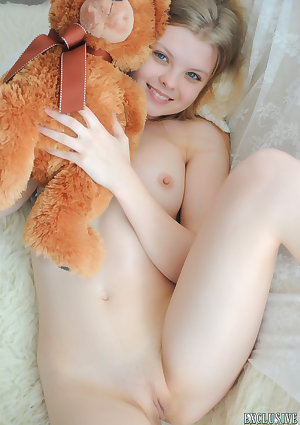 Tiny teen Kisa strikes tempting nude poses while holding a teddy bear