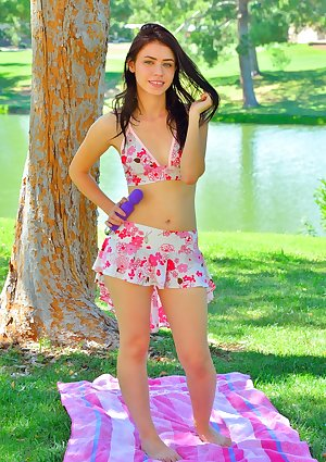 Pouty brunette opens her legs under a tree to insert a banana and vibrator