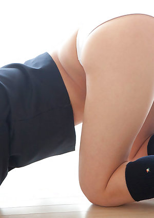 Asian in a pleated miniskirt lifts her top and shows off her beautiful tits